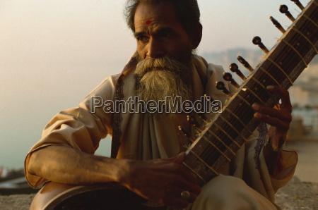 sitar and player beside the ganga