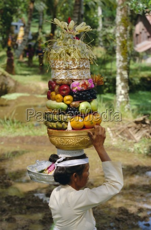 woman carrying food offerings on her