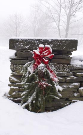 ein schneebedeckter weihnachtskranz aus tannenzweigen rote