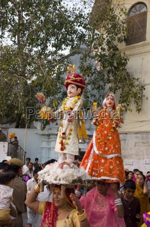 sari clad women carrying idols at