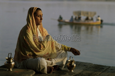 hindu woman meditating beside the river