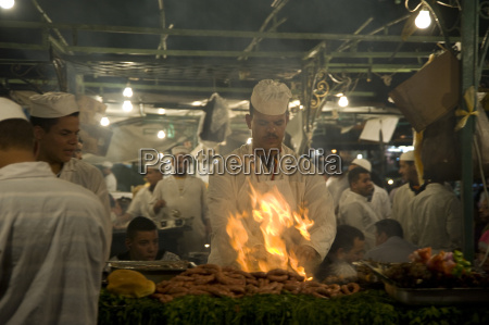 ein koch grillt fleisch an einem