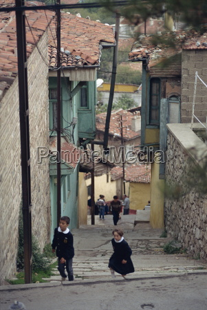 children climb steps in a narrow