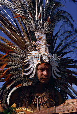 native american wearing large head dress