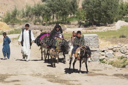 aimaq people walking and riding donkeys