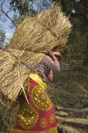 local woman carrying heavy bale of