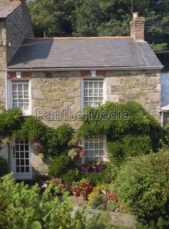 stone cottage with summer flowers in