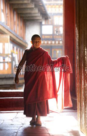 junge buddhistische moench in roten roben