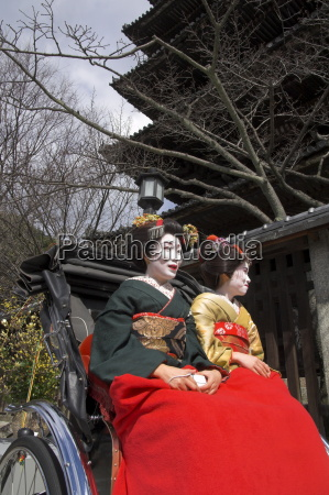 two geishas in traditional dress posing