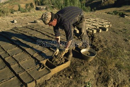 man making clay bricks for his