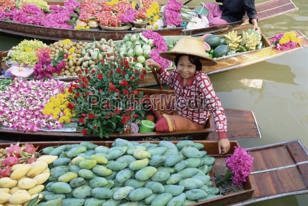 market trader in boat selling flowers