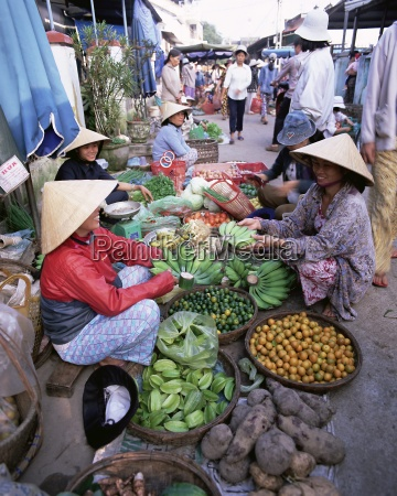 women in conical hats selling fruit