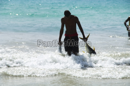 fisherman bringing catch onto beach at