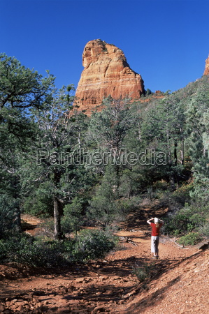 birdwatcher on path and red rock