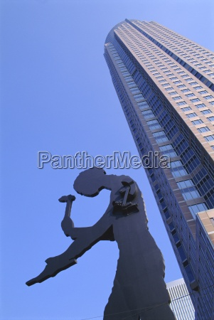 hammering man statue and fair tower
