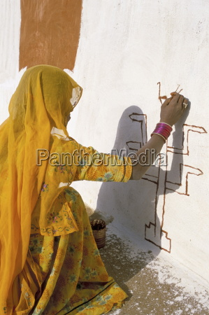 woman painting design on a wall