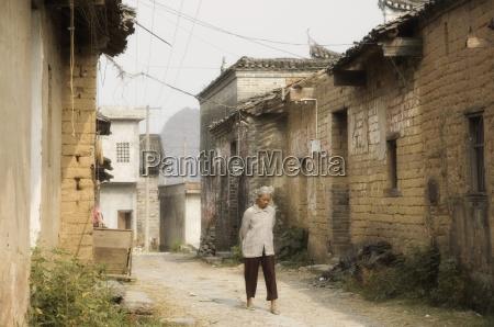 woman walking through village streets yangshuo