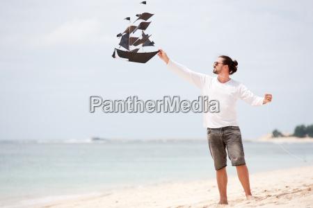 gluecklicher mann drachen kueste ozean fliegen