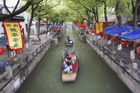 boats taking tourists along canal tongli