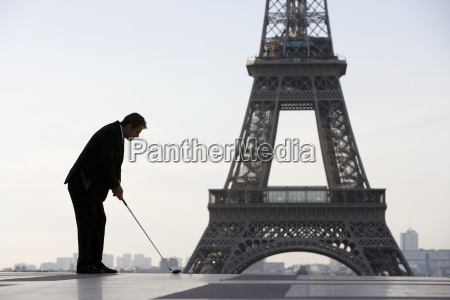 business man playing golf near the