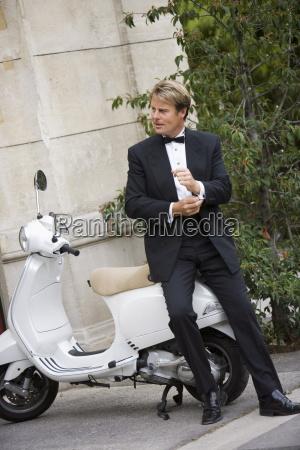 man arrives on scooter paris france