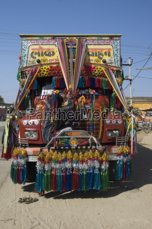 man fixing decoration onto truck for