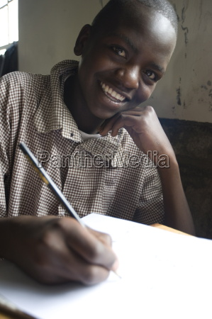 schoolboy working happily at school pupil