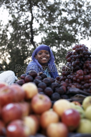 a girl selling fruit in the