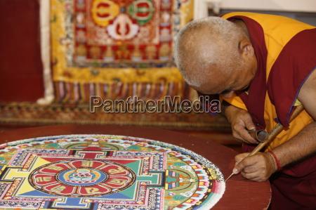 buddhistischer moench zeichnet ein mandala paris