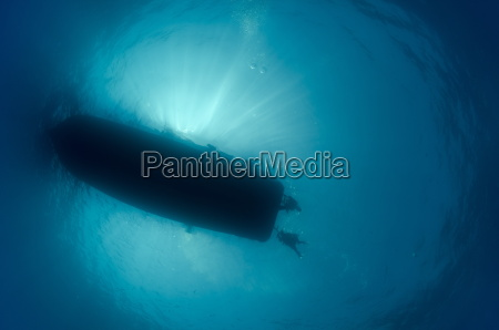 silhouette of dive boat with scuba