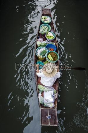 a vendor paddles their boat damnoen