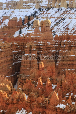 hoodoos with snow lit by late