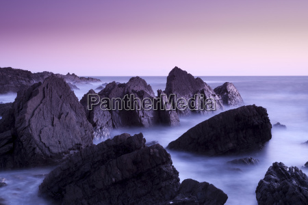 waves moving over jagged rocks at