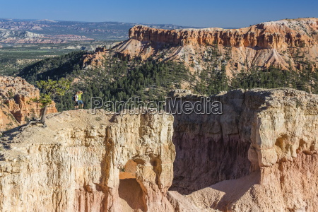 hikers on arch rock formation in