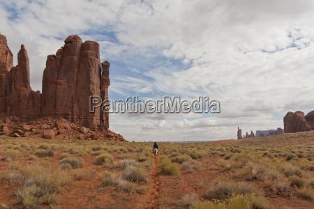navajo person rides a horse between
