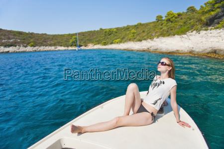 tourist sunbathing on a boat in