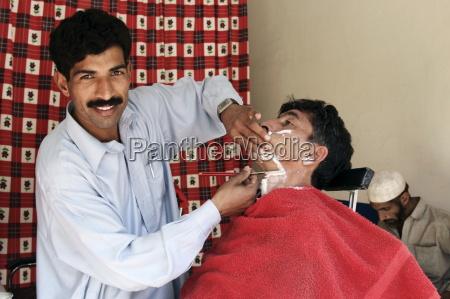 man visits barber shop in village