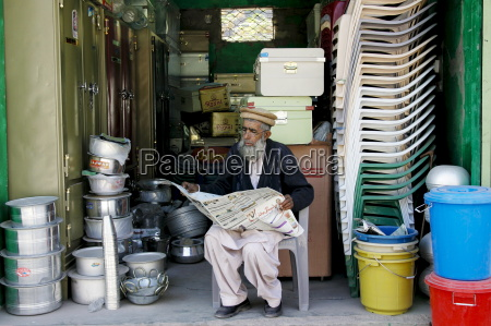 pakistani retailer sits reading newspaper in
