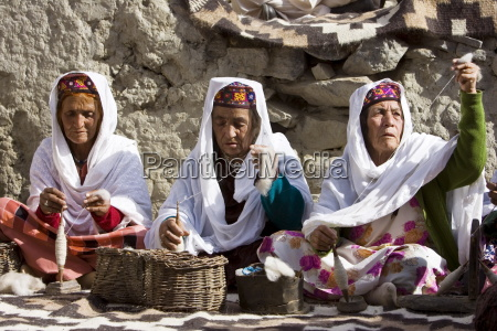 women spin wool together in mountain