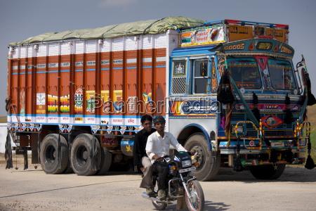indischer motorradfahrer reitet vorbei tata lastwagen