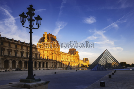 dawn light illuminates the louvre palace
