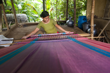a woman weaves traditional fabric using