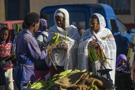 orthodox dressed woman buying vegetables asmara