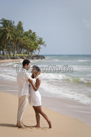 hispanic romantikpaar in weiss gekleidet am
