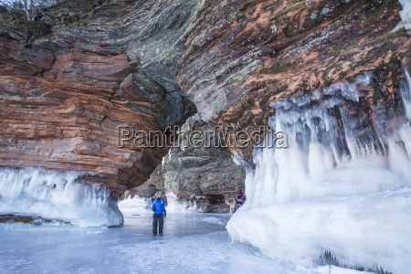 woman walks through sandstone arch while