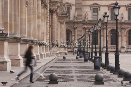 a woman walks through the louvre