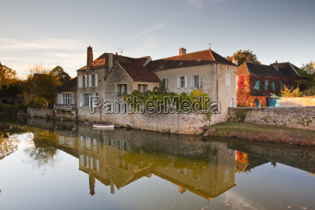 a house reflecting in the river