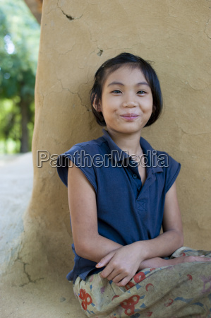 a girl from rangamati sits outside
