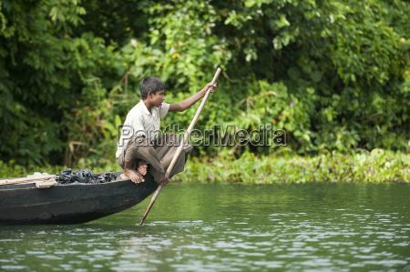 a boy paddles across kaptai lake