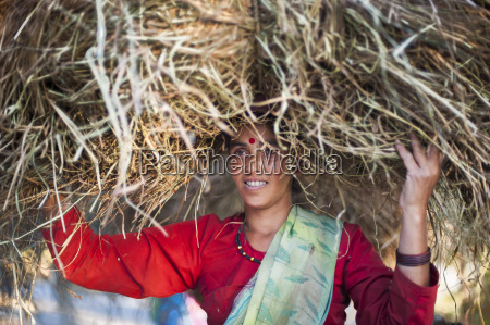 a woman carries a big pile